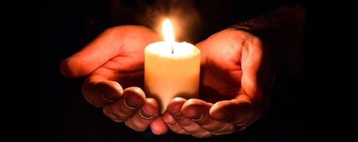Bild på två händer som håller ett brinnande ljus