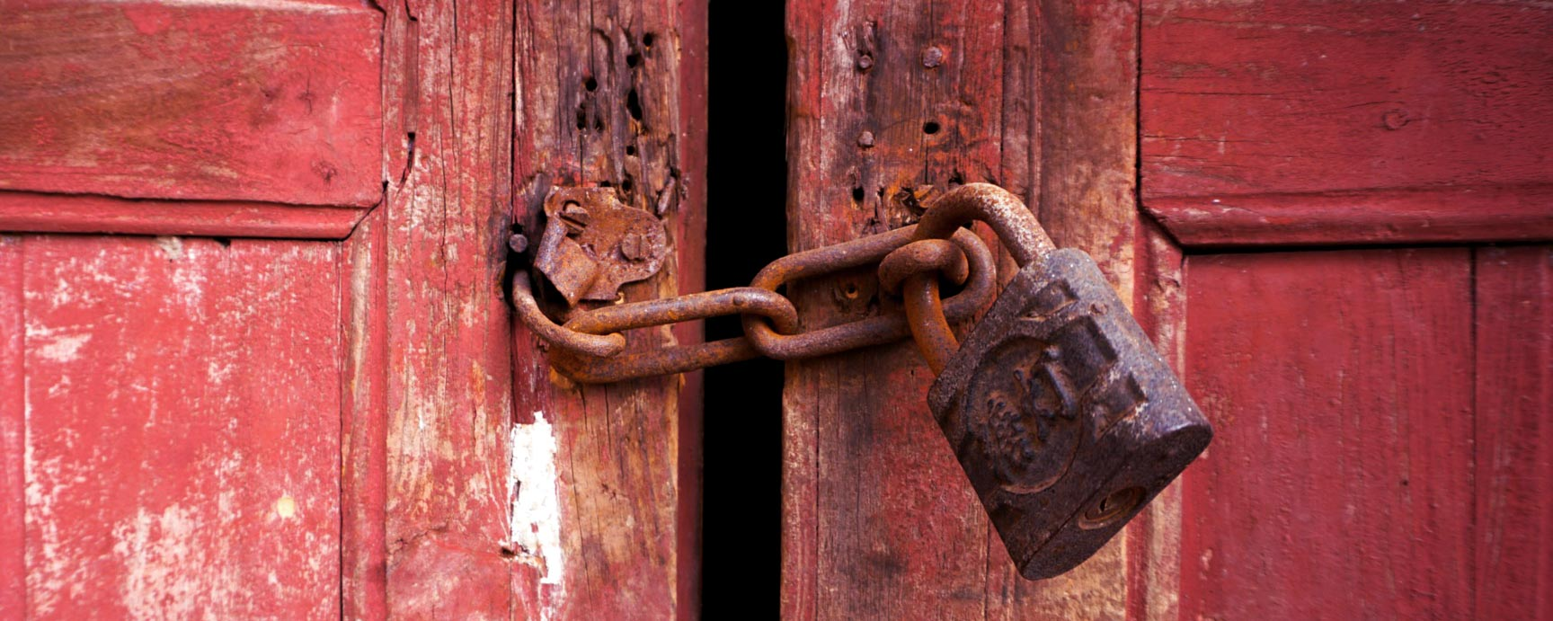 Bild på två röda dörrar som är låsta med en kedja och ett hänglås