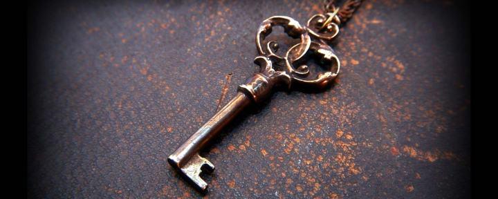 Nyckel med ornament som ligger på ett mörkt underlag