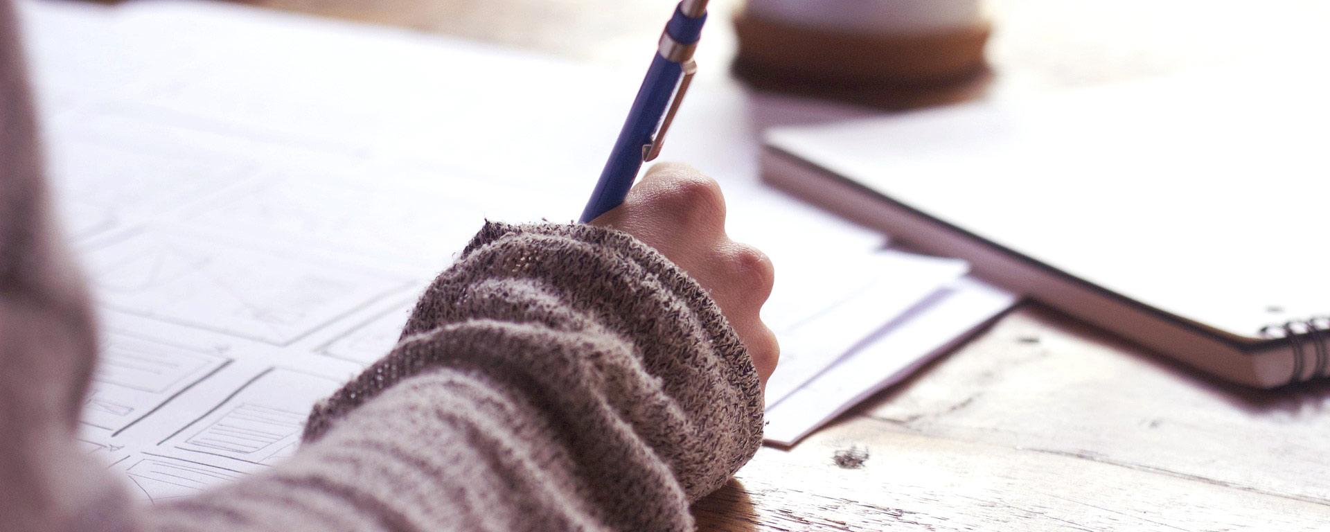 Bild på en hand som skriver på ett papper