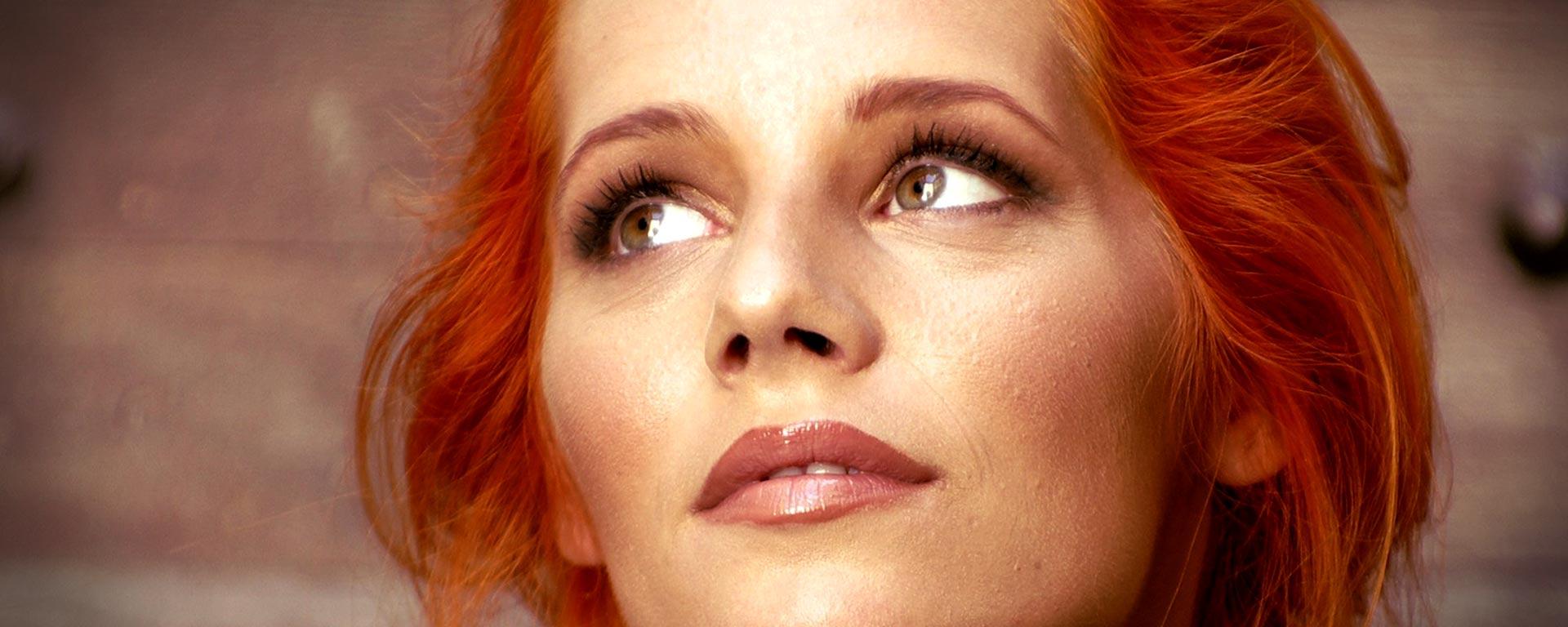 Porträtt på kvinna med rött hår som tittar uppåt vänster