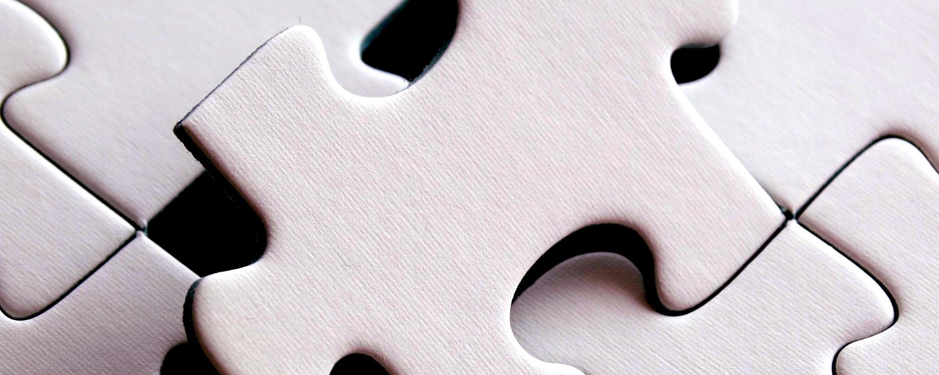 Bild på en vit pusselbit som sätts på plats bland andra pusselbitar