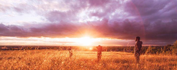 Bild på soluppgång med tre personer som står på en äng