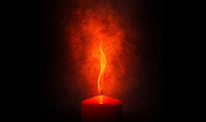 Ett tjockt rött ljus som brinner med en stor stark låga