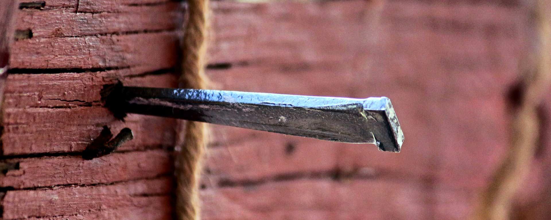 Stor spik som sitter i tvärslån på ett kors