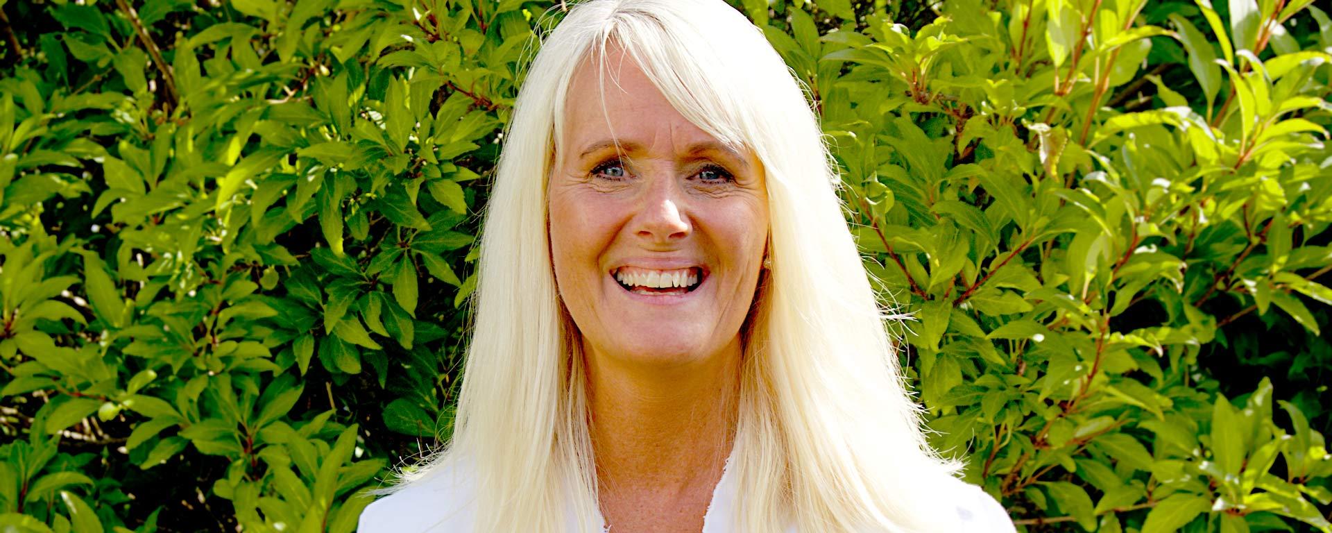 Porträtt av Eva-Lotta Bengtsson i solljus framför en häck